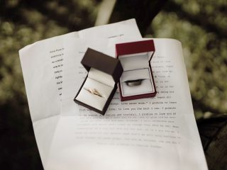 Wedding rings sitting on top of wedding vows