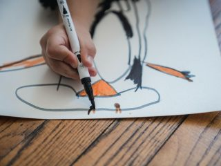 child drawing with a marker